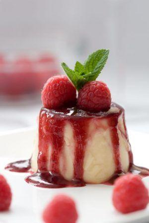 Delicious panna cotta dessert served with raspberries and a mint leave